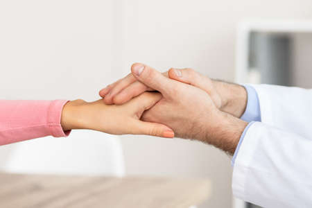 Empathy And Encouragement Concept. Close up of male doctor comforting female patient, holding hands during appointment at his office in hospital. General practitioner cheering young sick lady Foto de archivo