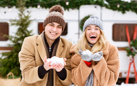 Young Couple In Love Playing With Snow While Having Fun Outdoors At Winter Day, Traveling With Caravan Home During Christmas Holidays, Holding Snowballs In Hands And Smiling At Camera, Free Space