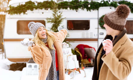 Winter Pastime. Young Cheerful Couple Having Fun Together Outdoors At Campsite, Throwing Snowballs At Each Other And Laughing, Playful Man And Woman Enjoying Christmas Holidays And Cold Weather