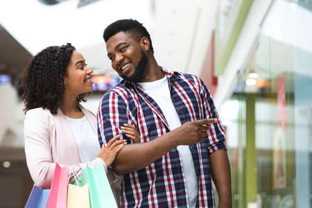 Beautiful black couple shopping together in modern department store, carrying bags with purchases and pointing at showcase in mall, enjoying seasonal sales and discount offers, free space