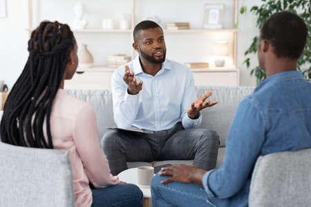 Family Psychotherapy. African American Couple Listening To Counselors Advices During Therapy Session In Office, Black Spouses Having Marital Counseling Meeting With Therapist, Selective Focus