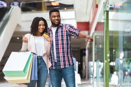 Couple On Shopping. Positive Black Spouses Making Purchases Together In Department Store, Pointing At Showcase In Mall, Man And Woman Holding Shopper Bags And Credit Card, Enjoying Seasonal Sales