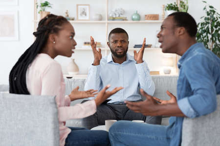Annoyed black psychologist watching couple arguing during marital therapy session, can not manage conflict, african american spouses quarreling in front of family counselor, selective focus