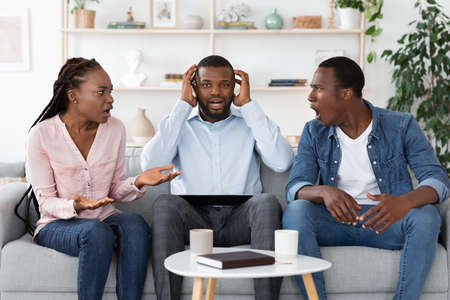 Shocked black marital counselor sitting between arguing spouses during therapy session, covering ears and looking at camera with despair, african american couple quarreling and blaming each other