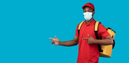 I Recommend. African american delivery guy wearing protective face mask and yellow thermo backpack, pointing away at copy space isolated on blue background. Advertisement concept, panorama, banner Foto de archivo