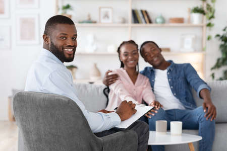 Family Psychotherapy. Happy Black Spouses And Marital Counselor Posing At Office After Successful Marital Therapy, Loving Couple Embracing On Couch And Therapist Smiling At Camera, Selective Focus