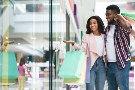Discount Prices. Smiling Black Couple Shopping In Mall Together, Looking At Showcase With Interest, African Spouses Walking In Department Store With Bright Shopper Bags, Enjoying Seasonal Sales