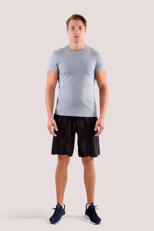 Full length portrait of young sporty guy in t-shirt and shorts standing on light studio background. Serious millennial sportsman looking at camera. Healthy lifestyle and sports concept Imagens