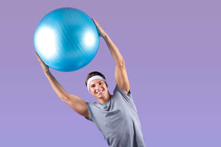 Positive young sportsman lifting fitness ball above his head, bending aside on lilac studio background, copy space. Portrait of happy millennial guy in sportswear doing aerobic workout