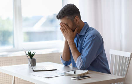 Remote Work Stress. Tired freelancer man sitting at desk with laptop at home office, overworked man covering face with hands, feeling fatigue and lack of inspiration, having problems with project Stock fotó