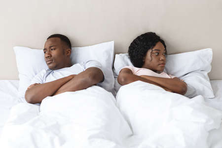 Young married african american couple after fight in bedroom, sad man and woman laying in bed apar. Upset black man and woman having fight, thinking about divorce or breaking up, home interior