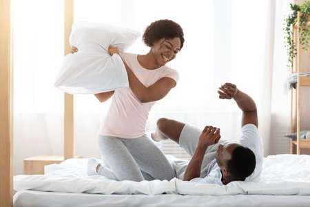Cheerful loving african-american couple fighting with pillows in bed, having fun together at home, empty space. Happy black man and woman having pillow fight in bedroom, enjoying weekend