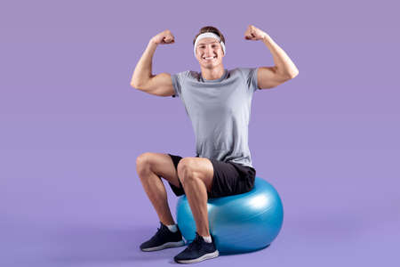 Positive young sportsman sitting on fitness ball and showing his strength on lilac studio background. Attractive millennial guy practicing aerobics or gymnastics, having strong biceps muscles 版權商用圖片