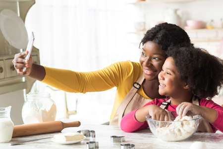 Beautiful black mom and little daughter taking selfie on smartphone in kitchen while baking together, kneading dough for cookies and having fun, cooking at home, enjoying homemade pastry, Banque d'images