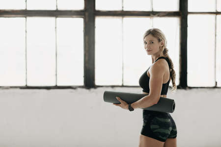 Slim body, start workout and coronavirus. Beautiful muscular mature female athlete coach blogger in sportswear with fitness tracker hold mat in gym interior with window and look at camera, free space