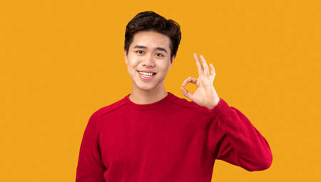 Everything Is Okay. Portrait of positive smiling asian guy doing approval ok gesture with fingers, showing that he is fine, isolated over orange studio background. Confident man is cool