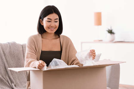 Satisfied Buyer. Portrait of smiling asian female customer opening and unpacking parcel cardboard box, sitting on the couch in living room at home. Young woman happy with delivery service