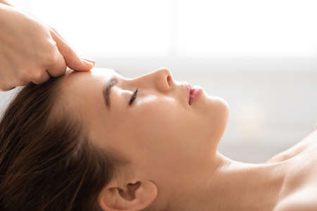 Unrecognizable masseuse massaging relaxed lady forehead, closeup. Attractive young woman having relaxing therapy at newest luxury spa salon, spending her weekend at spa, side view, copy space Standard-Bild