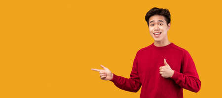 Look There. Smiling asian guy pointing his fingers away at copy space for your text or logo, isolated over orange studio background wall, banner, panorama. Smiling man showing thumbs up