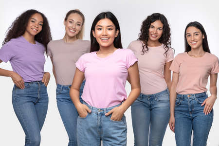 Asian Lady Standing With Group Of Happy Multiethnic Women Posing Smiling To Camera In Studio Over White Background. Female Diversity, Beauty And Friendship Concept. Stock Photo