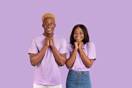 Excited black couple anticipating something wonderful, making wish, begging or praying over violet studio background. Hopeful African American guy and his girlfriend wishing for good luck