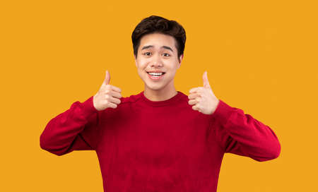 Best Choice, I Like It. Portrait of smiling asian guy showing thumbs up gesture with both hands, approving or recommending something good. Man posing isolated over orange studio background Standard-Bild