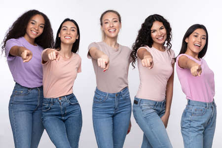 Youre Next. Positive Diverse Females Group Pointing Finger At Camera Smiling Posing Over White Studio Background. We Choose You Concept. Advertisement Banner Stock Photo