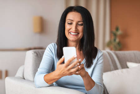 Weekend Pastime. Portrait of smiling mature lady holding smart phone, typing sms message, sitting on the couch at home. Communication Concept. Happy woman surfing internet, watching funny video