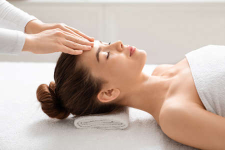 Acupressure head massage for beautiful young woman at thai spa salon, side view. Spa attendant making relaxing massage for lady wrapped in white towel, pressing on her forehead, copy space