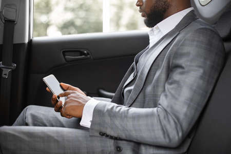 Cropped of black businessman going by company car to business meeting, holding mobile phone, copy space. African american entrepreneur siting on back car seat with smartphone, side view 版權商用圖片