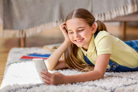 Amazing Application. Portrait of positive glad teenage kid with ponytails using smart phone, chatting, typing and sending message, watching funny video, lying on the floor carpet at home