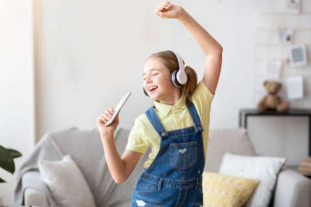 Having Fun. Portrait of overjoyed teen girl singing song and using smart phone as microphone, wearing wireless headset. Carefree schoolgirl dancing at home in living room, copy space Standard-Bild