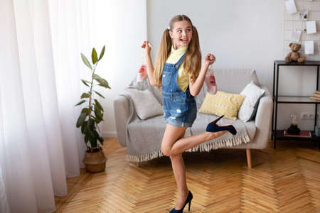 Having Fun. Full length shot of excited female teenager with two ponytails wearing and posing in blue high heels shoes, holding pink sneakers by laces, standing in living room, looking away