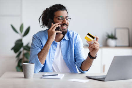 Easy Payments. Happy Indian Freelancer Guy Holding Credit Card And Talking On Cellphone While Sitting At Desk In Home Office, Making Mobile Payment, Speaking With Customer Service Manager, Free Space