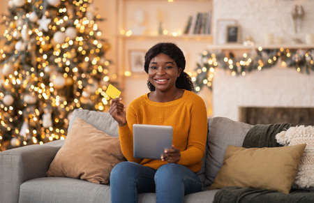 Seasonal sales and quick online shopping before holidays. Smiling young african american lady with tablet, showing credit card in cozy home interior with luminous garlands, copy space