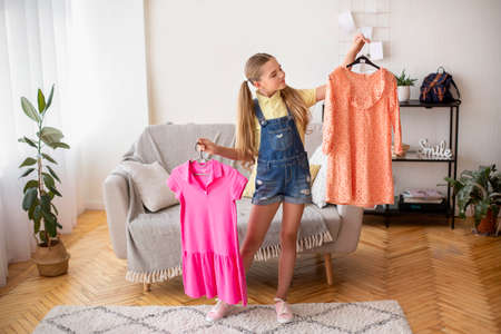 New Clothes. Full length portrait of young teenage girl standing in living room, choosing stylish outfit, holding hangers with two bright dresses in both hands, deciding what to wear