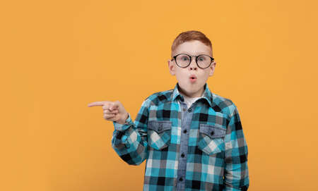 Amazed kid with glasses showing shocking advertisement, aiming at copy space for text or advertisement. Surprised redhead schoolboy pointing at empty space over yellow studio background, panorama