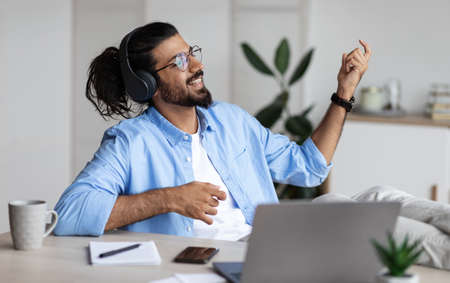 Be Yourself. Joyful weatern freelancer guy listening music in headphones and playing virtual guitar, relaxing at desk in home office, young indian man having fun and enjoying working remotely