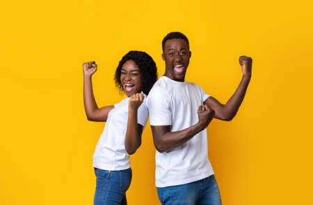 Emotional african american young couple celebrating success on yellow studio background. Happy black man and woman clenching fists and screaming, won the prize or got exciting news