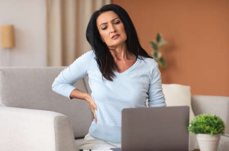 Tired Of Work. Portrait of mature lady having back pain while sitting on the couch at home, suffering from tension and acute spinal ache, feeling uncomfortable, stressed woman using laptop Stockfoto