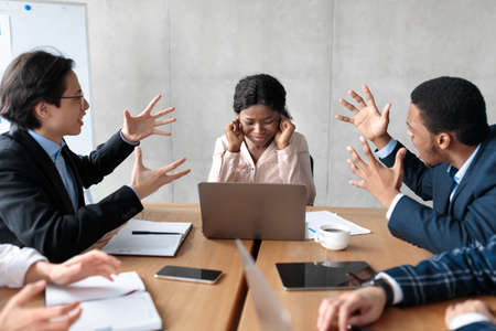 Angry Coworkers Shouting At Female Colleague Discontented With Her Work During Corporate Meeting In Modern Office. Bullying And Victimization At Workplace, Disagreement And Conflicts