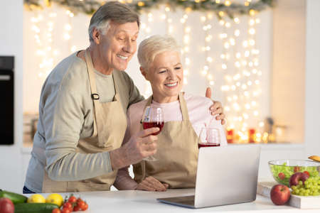 Mature Couple Making Video Call Celebrating Christmas At Laptop Having Virtual Xmas Party Online Enjoying Wine And Distant Communication Sitting In Modern Kitchen At Home. Quarantine New Year Holidays