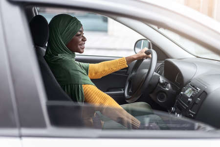 Car Leasing Concept. Happy Black Religious Woman In Hijab Driving Modern Vehicle, Young Female African Driver In Headscarf Enjoying Ride In Ger New Automobile, Through Window Shot, Side View