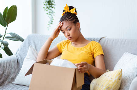 Wrong Item Concept. Sad unpset african american lady sitting on couch and unpacking cardboard box, received parcel with damaged staff, feeling dissatisfied and disappointed with bad purchase