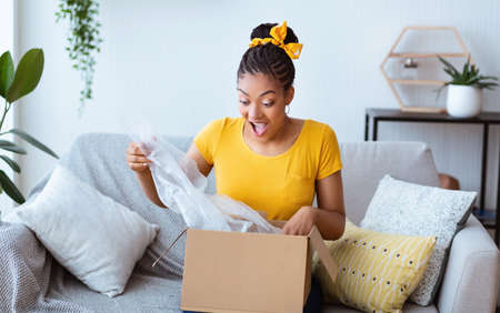 Fast Delivery. Overjoyed black woman received package, unpacking cardboard box, sitting on the sofa in living room at home, free space. Female buyer excited about her online shopping purchase
