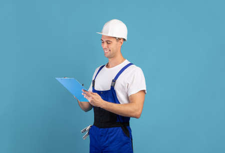 Smiling male home repair contractor in coveralls and hardhat writing notes in clipboard, professional handyman planning budget for house improvement, standing over blue studio background, copy space