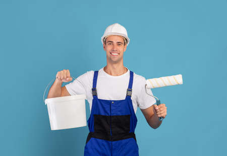 Painter Guy. Smiling Young Male Repair Master Wearing Coveralls Holding Bucket And Equipment For Painting Standing Over Blue Studio Background, Happy Man In Hard Hat Ready For Renovation, Free Space