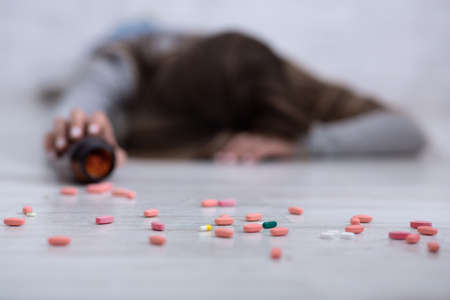 Young woman committing suicide, lying on floor with tablets scattered from jar, selective focus. Depression and drugs overuse, mental illness or psychological disorder concept Stock Photo