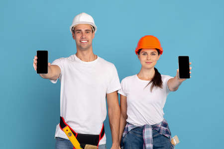 Smiling young man and woman in hardhats demonstrating smartphones with black screen, showing free copy space for your app or website design, standing over blue studio background, mockup image