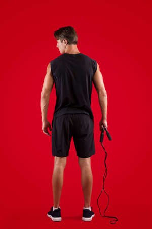 Aerobic workout. Back view of strong young man standing with skipping rope on red studio background. Full length portrait of motivated athlete warming up before training, doing cardio exercises